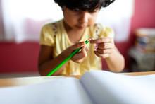 A Little Girl Sharpens A Pencil