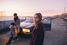 Portrait Of Girl On Road With Family Standing By Car In Background