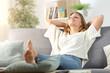 Leinwandbild Motiv Carefree woman relaxing sitting on a sofa at home