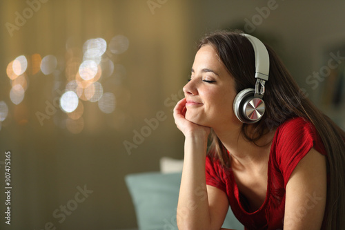 Relaxed woman listening to music at home in the night - 307475365