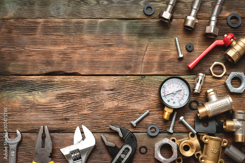 Fototapeta Plumbing flat lay background with copy space. Work tools and pipeline parts on plumber workbench. obraz