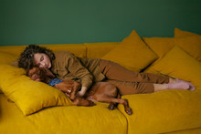 Portrait Of Beautiful Curly Girl With Freckles Sleeping With A Dog Embracing On A Yellow Couch