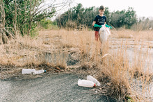 Boy Picking Up Trash For Earth...