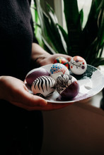 Close Up Of Woman's Hands Holding Plate Of Decorated Easter Eggs