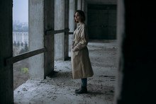 Portrait Of A Serious Girl In A Coat On The Floor Of An Abandoned Building With An Evening City In The Frame
