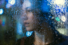 Portrait Of Young Woman Looking Through Wet Glass