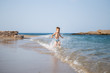 A little cute boy runs along the beach and plays. Happy kid at sea. Vacation at sea with children. Greece