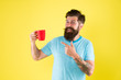 canvas print picture - True specialty coffee is becoming big business. Energy concept. Hipster barista yellow background. Coffee shop. Bearded man drink morning coffee. Tea time. Cappuccino with right proportion of milk