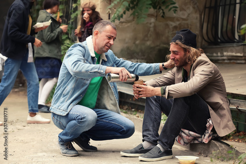 Volunteer giving drink to homeless man outdoors Canvas Print
