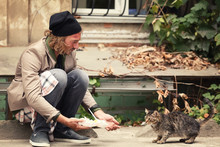 Poor Man Sharing Food With Homeless Cat Outdoors