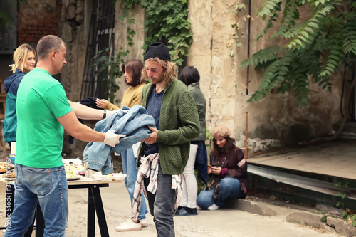 Volunteers giving clothes and food to homeless people outdoors Canvas Print