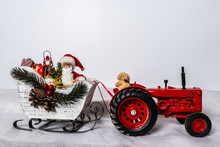 Santa In Sleigh Being Pulled By Teddy Bear On Red Tractor