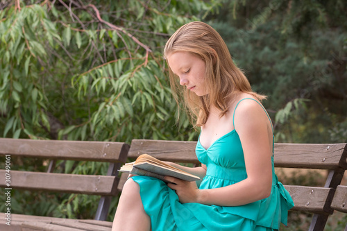 A schoolgirl in a turquoise dress is reading a fascinating book on a bench in a summer park Wallpaper Mural
