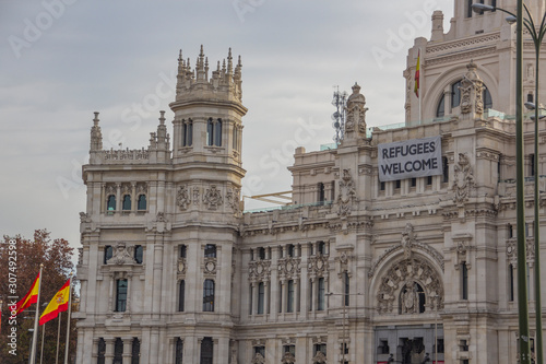 Photo Welcome Refugee message on Palacio de Cibeles in Madrid with spain flags
