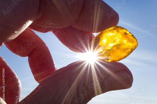 Photo male hand holds amber against the sun
