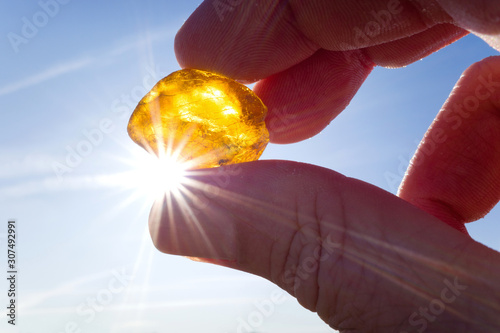 Foto male hand holds amber against the sun