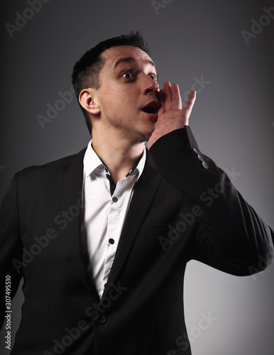 Excited shouting young business man gesturing the hands loudspeaker sign in celebrating emotion with wide open mouth to agitate on grey background Canvas Print