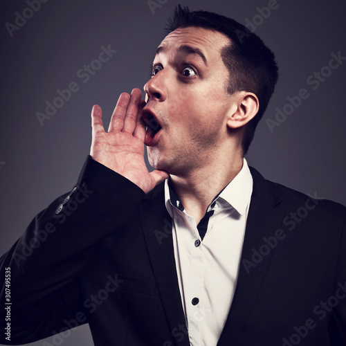 Excited shouting young business man gesturing the hands loudspeaker sign in celebrating emotion with wide open mouth to agitate on grey background Wallpaper Mural