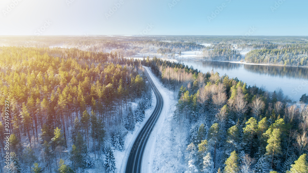 Fototapeta White car drives empty road running along the beautiful blue lake in the cold Finnish winter. Tourists on road trip cruising through the idyllic snow covered countryside and woods.