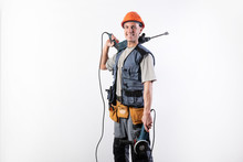 A Builder With A Hammer Drill On His Shoulder, And A Angle Grinder In His Other Hand, In A Helmet, Smiles.