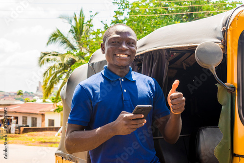 Obraz na plátne cheerful african man standing next to his tuk tuk taxi smiling and using his sma