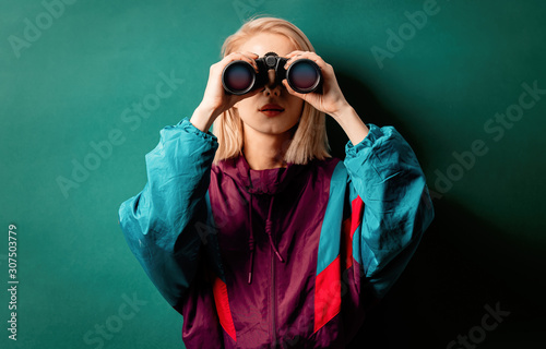 Photo Style woman in 90s punk clothes with binoculars on aqua menthe color background