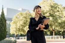 Young Blond Businesswoman Wearing Black Sailor's Cap And Holding Laptop Bag