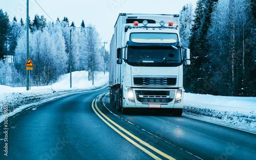 fototapeta na szkło Winter road with snow. Truck in Finland. Lorry car and cold landscape of Lapland. Europe forest. Finnish City highway ride. Roadway and route snowy street trip. Delivery in downhill driveway driving