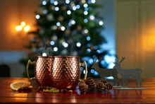 Close-up Of Mulled Wine With Food And Decorations On Table Against Illuminated Christmas Tree At Home