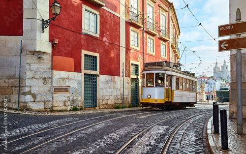 Lisbon, Portugal. Vintage yellow retro tram on narrow bystreet tramline. Red houses in Alfama district of old town. Popular touristic attraction of Lisboa city.