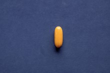 Overhead Shot Of An Orange Pill On A Dark Blue Surface