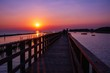 wooden pier at the sea with beautiful bloody sunset. sunset seascape at a wooden jetty. Wood bridge
