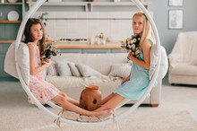 Two Adorable Children In Beautiful Dresses Sitting In Swing In Interior Studio With Bed And Kitchen On Background.