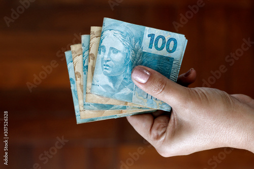 Hands holding Brazilian real notes - Money from Brazil - Notes of Real - Brazil BRL banknote
