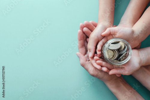 Fotografía child and adult holding money jar, donation, saving concept, new year resolution