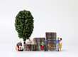 canvas print picture - A variety of miniature people and pile of coins with miniature tree.