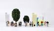 canvas print picture - Any of various miniature families standing in front of miniature trees and miniature building.