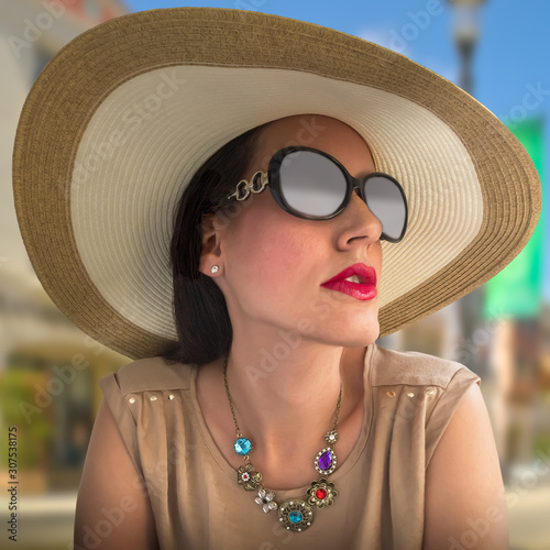 A sophisticated socialite wearing a large rim straw hat and big sunglasses looks up at the Plaza Wallpaper Mural