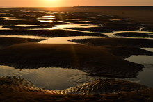 A Small Puddles In The Sand After Low Tide In Sunset Light