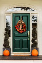 Green Front Door With Fall Autumn Wreath With Leaves And Topiaries And Pumpkins