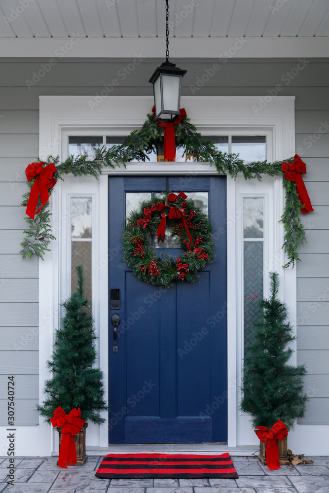 Fototapeta Navy blue front door of contemporary new construction siding gray home decorated for Christmas holidays with wreath trees and garland