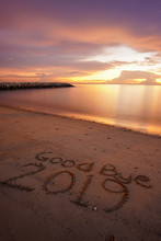 Welcoming New Year Concept. Good Bye 2019 Written On Sandy Beach With Beautiful Sunset Background.