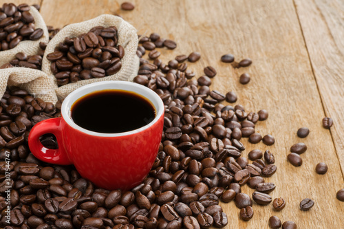Fototapety, obrazy: Black coffee in a red coffee cup and roasted coffee beans placed on a wooden table top view