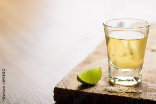 Fotografía Tequila in a shot glass on a brown wooden background prepared for a party