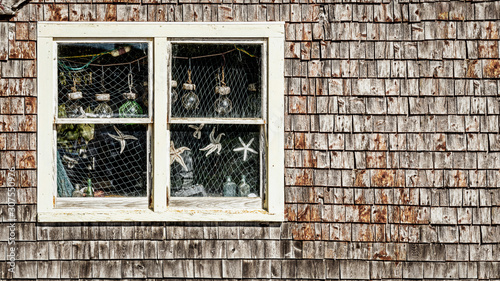 Fényképezés  A window with curious ocean oddities at the Peggy's Cove village in Nova Scotia,