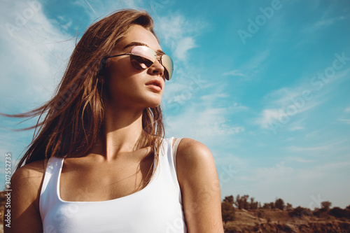 Beautiful girl in a white shirt and classic aviator sunglasses posing in the desert during the sunset Canvas Print