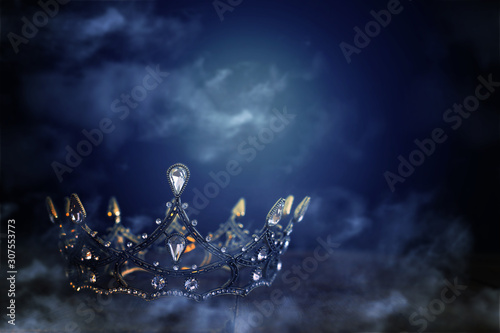 low key image of beautiful queen/king crown over wooden table. vintage filtered. fantasy medieval period. mist and fog