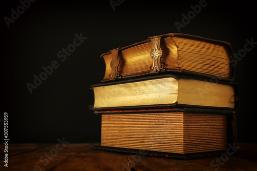 Spoed Foto op Canvas Europa stack of antique books on old wooden table. fantasy medieval period and religious concept.