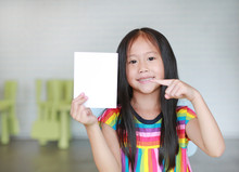 Portrait Little Smiling Asian Child Girl Holding Blank White Paper Card In Her Hand With Pointing. Kid Showing Empty Paper Note Copy Space In Children Room.