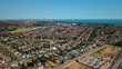Aerial drone footage over Thorpe bay showing shoebury garrison a yacht club showing summer drought yellow grass and rows of houses blue sky's blue sea's housing estate